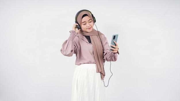 Azjatycka kobieta w hidżabie słucha, patrząc na ekran swojego telefonu na białym tle