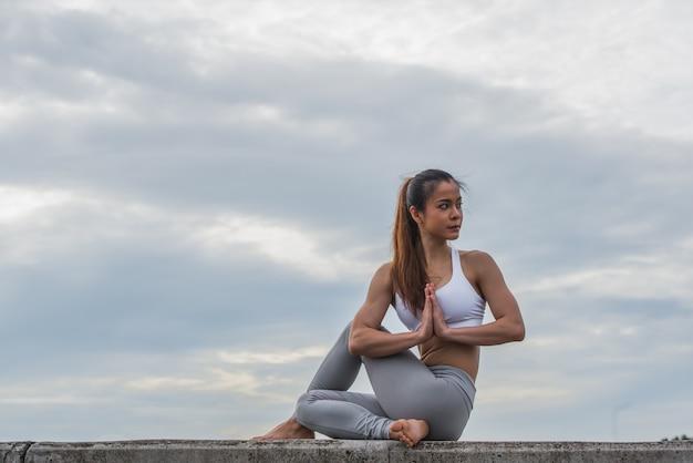 Azjatycka kobieta w joga pozie na górze ściany.
