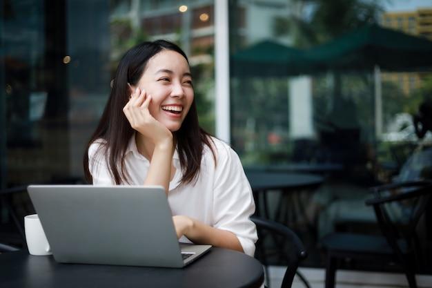 Azjatycka kobieta w kawiarni pracuje na laptopie
