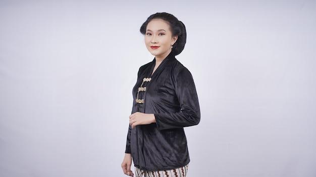 Azjatycka kobieta w kebaya stojąca ukośnie wygląda pięknie na białym tle