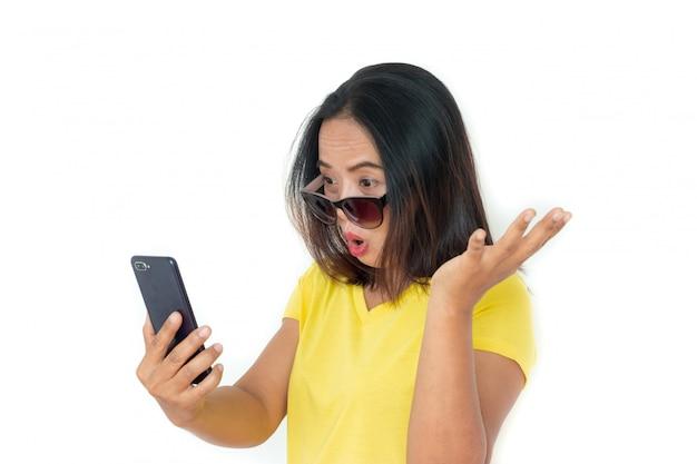Azjatycka kobieta w koszulce z smartphone nad bielem