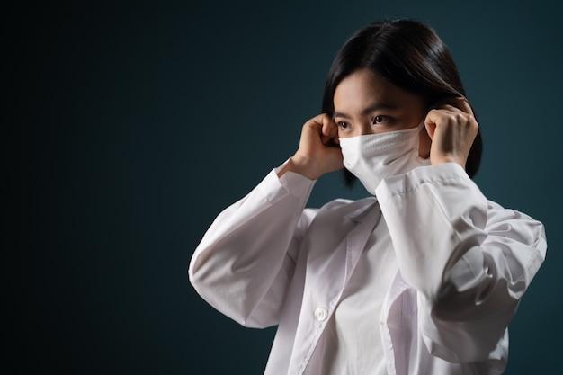 Azjatycka kobieta w mundurze medycznym noszenie maski ochronnej odizolowane na niebiesko