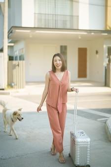 Azjatycka kobieta w nowym domu. wyciągnij bagaż i podejdź do drzwi domu.
