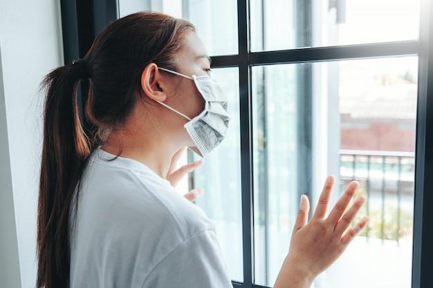 Azjatycka kobieta w odosobnieniu w domu z powodu wybuchu wirusa koronawirus noszący maskę kwarantanny
