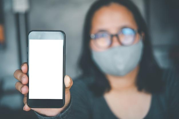 Azjatycka kobieta w okularach i masce higienicznej zostaje podniesiona z pustym białym ekranem pulpitu