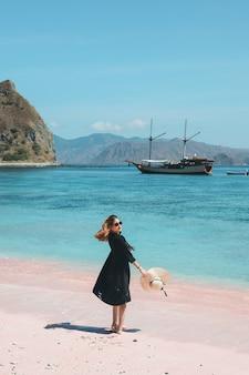 Azjatycka kobieta w okularach przeciwsłonecznych trzyma letni kapelusz, ciesząc się wakacjami na różowej plaży z łodzią