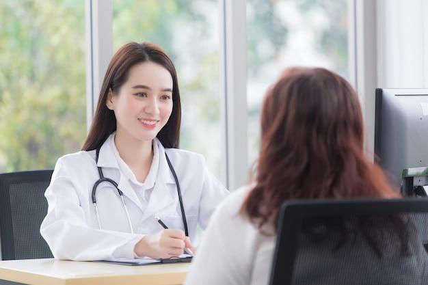 Azjatycka kobieta w podeszłym wieku pacjentka konsultuje się z lekarzem w sprawie jego objawu, podczas gdy lekarz daje