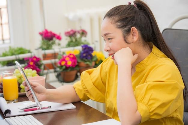 Azjatycka kobieta w przypadkowej odzieży pracuje z telefonem i laptopem komunikować się w internecie z klientami w pokoju.