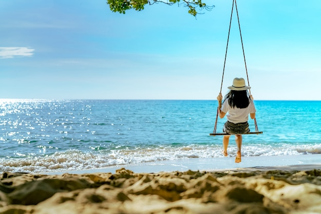 Azjatycka kobieta w przypadkowym stylu odzieży kapeluszu huśtawce huśtawki przy piasek plażą i patrzeć pięknego tropikalnego raju morze i niebo na zmierzchu. letni wypoczynek. letnie wibracje.