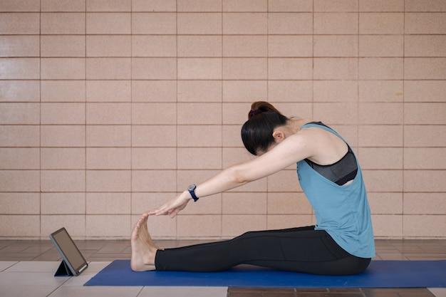 Azjatycka kobieta w sportowym stroju trenuje po programie treningowym online za pomocą cyfrowego tabletu w domu