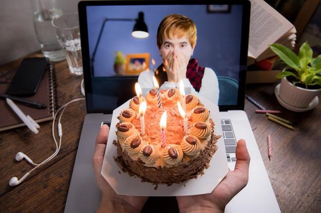 Azjatycka kobieta w średnim wieku czuje się szczęśliwa, świętując wirtualne urodziny za pośrednictwem połączenia wideo