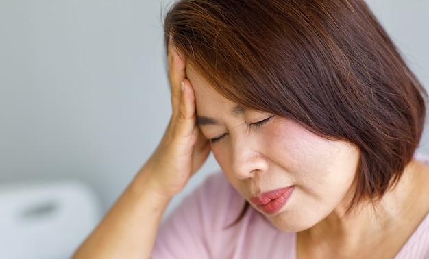 Azjatycka kobieta w średnim wieku, która odczuwa ból spowodowany nagłym bólem głowy i atakiem udaru mózgu, trzyma się za głowę ze zestresowaną twarzą. pojęcie problemu mózgu i głowy.