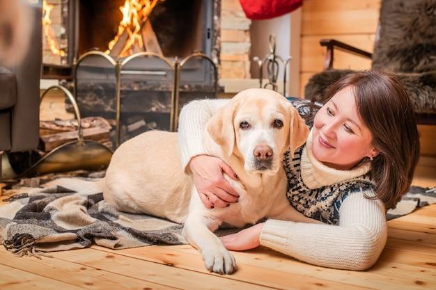 Azjatycka kobieta w średnim wieku obejmuje psa labradora leżącego na kocu przed kominkiem w wiejskim domu.