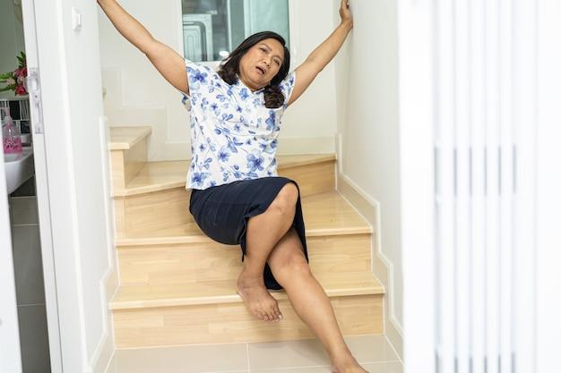 Azjatycka kobieta w średnim wieku pacjentka spada ze schodów, ponieważ śliskie powierzchnie