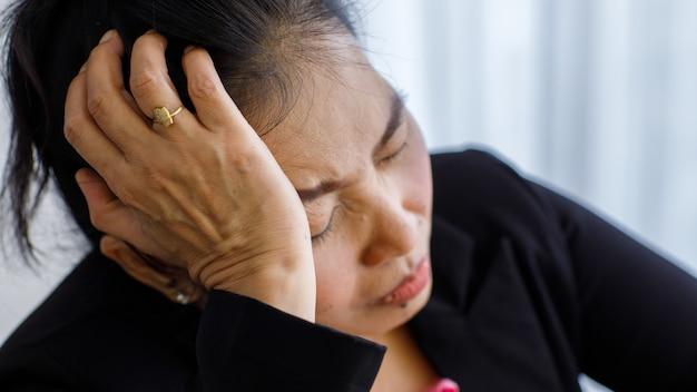 Azjatycka kobieta w średnim wieku, starsza kobieta, odczuwa ból i cierpi na nagły ból głowy oraz atak udaru mózgu i trzyma się wokół głowy ze zestresowaną twarzą. pojęcie problemu mózgu i głowy.