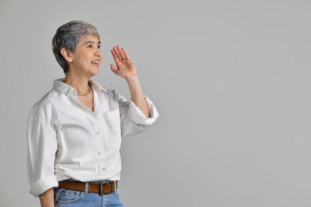 Azjatycka kobieta w średnim wieku trzyma rękę przy ustach i mówi sekret na białym tle