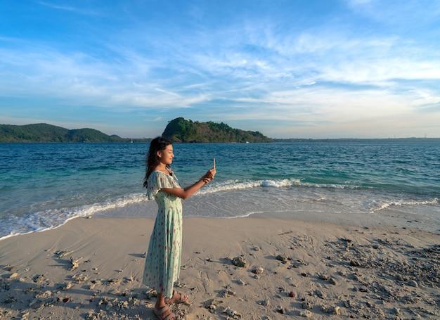 Azjatycka kobieta w sukience maxi stojąca trzymająca i oglądająca mały koral na plaży na wyspie z błękitnym morzem i niebem z ciepłym światłem słonecznym, dziewczyna relaksuje się na wakacjach latem na wyspach rayang, rayong, tajlandia