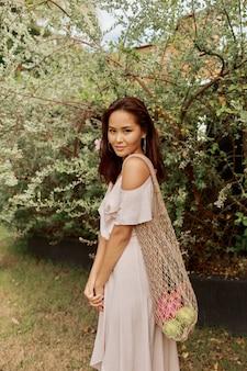 Azjatycka kobieta w sukni trzyma ekologiczną siatkową torba na zakupy z świeżymi tropikalnymi owoc.