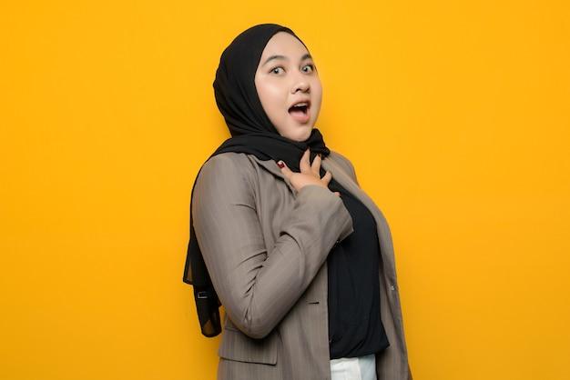 Azjatycka kobieta w szoku na żółtym tle