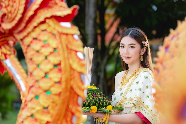 Azjatycka kobieta w tradycyjnym stroju tajskim posiadają festiwal kratong loy krathong