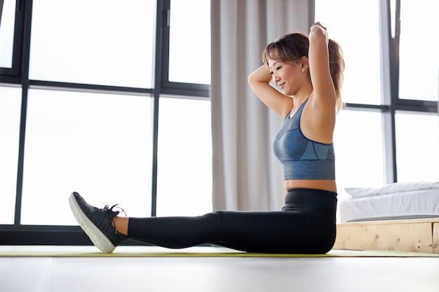 Azjatycka kobieta wiąże włosy w koński ogon przed ćwiczeniami, siedząc na macie i ciesząc się zdrowym stylem życia