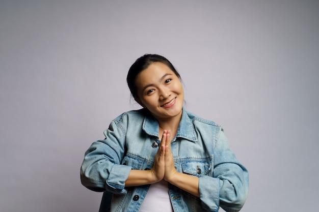 Azjatycka kobieta winna trzymając się za ręce w modlitwie stojącej na białym tle.