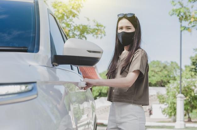 Azjatycka kobieta wsiada do samochodu w masce medycznej