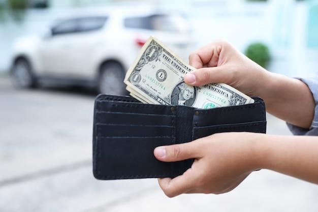 Azjatycka kobieta wyciągająca pieniądze z czarnej torebki