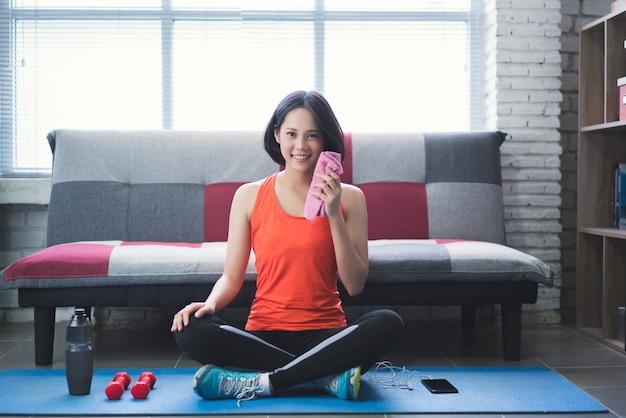 Azjatycka kobieta wyciera jej pot po treningu w domu.