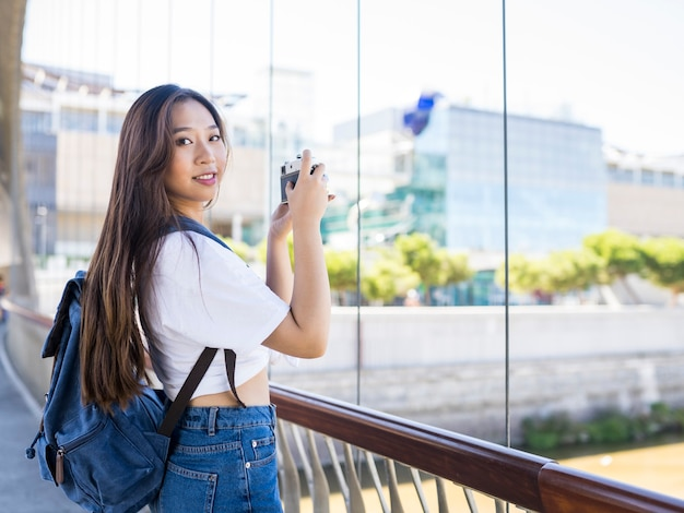 Azjatycka kobieta z aparatem i plecakiem w mieście