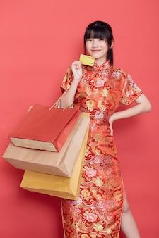 Azjatycka kobieta z chińską sukienką trzyma kartę kredytową i torby na zakupy