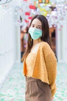 Azjatycka kobieta z długimi włosami nosi pomarańczową dzianinę i medyczną maskę na twarz w koncepcji opieki zdrowotnej