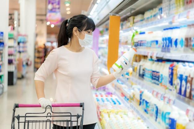Azjatycka kobieta z higieniczną maską i gumową rękawiczką z koszykiem w sklepie spożywczym i szukająca codziennego świeżego mleka do kupienia podczas wybuchu covida-19 w celu przygotowania do pandemicznej kwarantanny