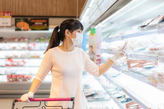Azjatycka kobieta z higieniczną maską i gumową rękawiczką z koszykiem w sklepie spożywczym i szukająca paczki świeżego mięsa do kupienia podczas wybuchu covid-19 na przygotowania do pandemicznej kwarantanny