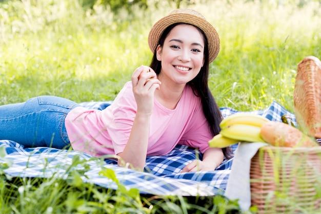 Azjatycka kobieta z jabłczanym lying on the beach na koc