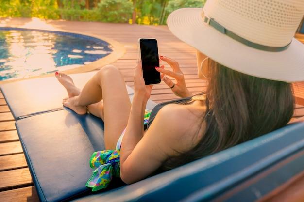 Azjatycka kobieta z kapeluszu i swimsuit obsiadaniem w krześle przy poolside i używać smartphone na wakacje.