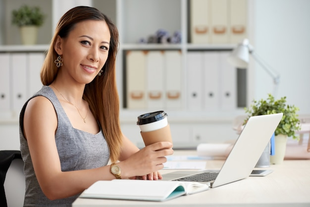 Azjatycka kobieta z kawą na wynos w biurze