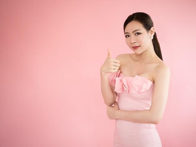 Azjatycka kobieta z kciukiem up, seksowny dziewczyny przedstawienia palec na różowym tle
