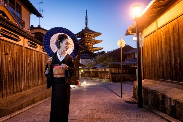 Azjatycka kobieta z kimonowym odprowadzeniem przy yasaka pagodą w kyoto