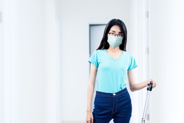 Azjatycka kobieta z maską i okularami stojąc z walizką w szpitalu. badanie lekarskie przed podróżą