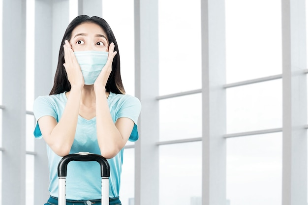 Azjatycka kobieta z maską na twarz z walizką w szpitalu. badanie lekarskie przed podróżą