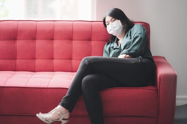 Azjatycka kobieta z maską ochronną śpi na kanapie, czując się zmęczona i chora