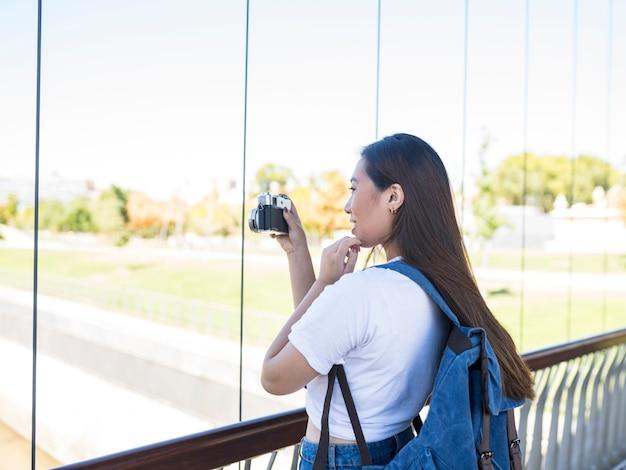 Azjatycka kobieta z plecakiem, robiąc zdjęcia po mieście