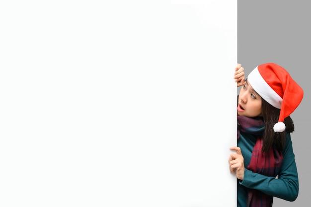Azjatycka kobieta z santa kapeluszowym zerkaniem nad reklamy pustego miejsca sztandarem
