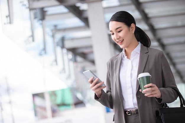 Azjatycka kobieta z smartphone stojąc przed ulicą niewyraźne budynku. moda biznesowa fotografia piękna dziewczyna w swobodnym apartamencie z telefonem i filiżanką kawy