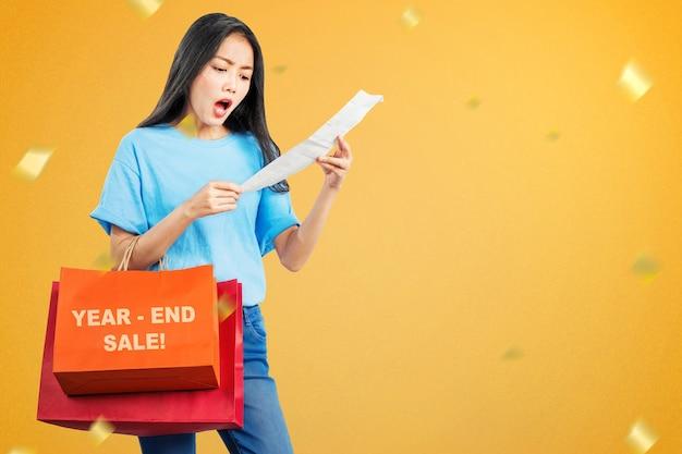 Azjatycka kobieta z torby na zakupy w szoku po zakupach na wyprzedaży na koniec roku. szczęśliwego nowego roku 2021