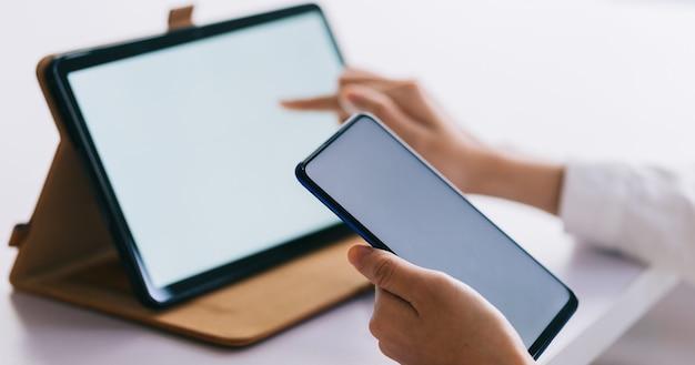 Azjatycka kobieta za pomocą smartfona i tabletu z pustym ekranem