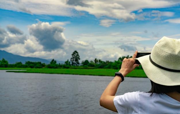 Azjatycka kobieta za pomocą smartfona zrobić zdjęcie pięknego krajobrazu rzeki, góry i lasu. letnia wycieczka wakacyjna. modniś kobieta z minimalnym stylowym plenerowym aktywnością dla relaksuje życia.