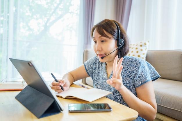Azjatycka kobieta za pomocą tabletu, oglądając lekcję kurs języka migowego online komunikuje się przez wideokonferencję z domu, koncepcja edukacji e-learningowej
