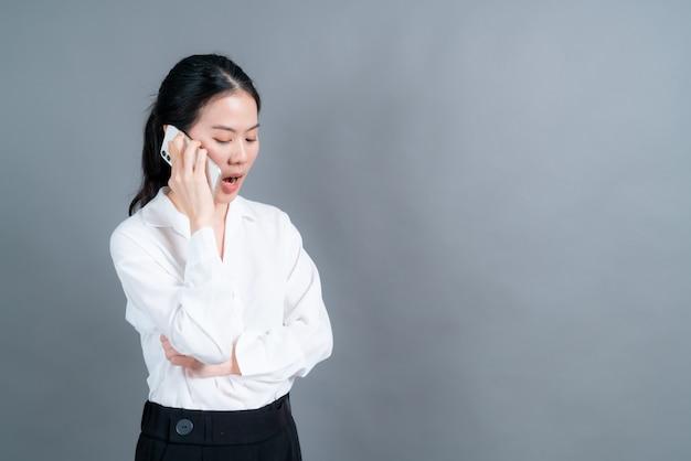 Azjatycka kobieta za pomocą telefonu komórkowego rozmawia biznes na białym tle